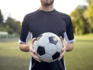 man holding football on pitch